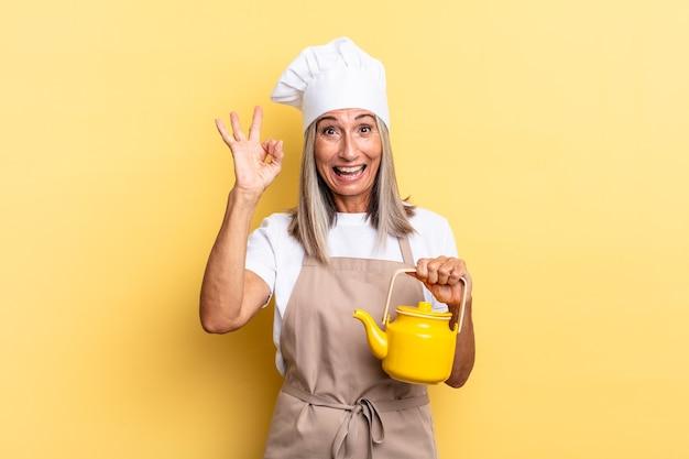 Köchin mittleren alters, die sich glücklich, entspannt und zufrieden fühlt, zustimmung mit okayer geste zeigt, lächelt und eine teekanne hält