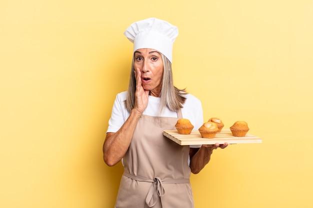 Köchin mittleren alters, die sich schockiert und verängstigt fühlt, mit offenem mund und händen auf den wangen verängstigt aussieht und ein muffins-tablett hält?