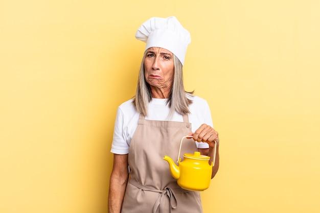 Köchin mittleren alters, die sich traurig und weinerlich mit einem unglücklichen blick fühlt, mit einer negativen und frustrierten einstellung weint und eine teekanne hält