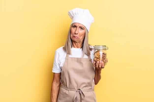 Köchin mittleren alters, die sich traurig und weinerlich mit einem unglücklichen blick fühlt und mit einer negativen und frustrierten einstellung mit keksen weint