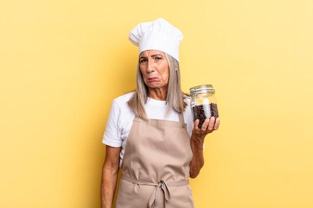 Köchin mittleren alters, die sich traurig und weinerlich mit einem unglücklichen blick fühlt und mit einer negativen und frustrierten haltung weint, die kaffeebohnen hält