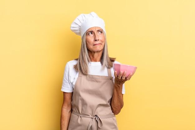 Köchin mittleren alters, die sich traurig, verärgert oder wütend fühlt und mit einer negativen einstellung zur seite schaut, die stirn runzelt und einen leeren topf hält