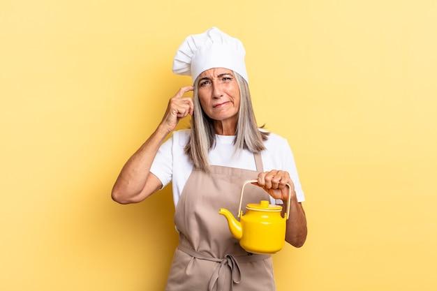 Köchin mittleren alters, die sich verwirrt und verwirrt fühlt, den kopf kratzt und zur seite schaut und eine teekanne hält