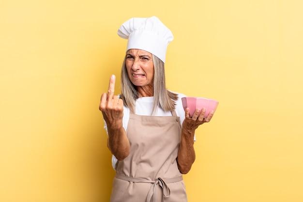 Köchin mittleren alters, die sich wütend, verärgert, rebellisch und aggressiv fühlt, den mittelfinger dreht, sich wehrt und einen leeren topf hält