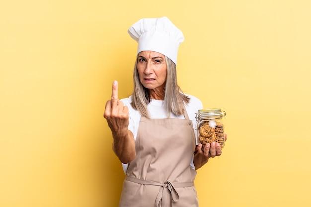 Köchin mittleren alters, die sich wütend, verärgert, rebellisch und aggressiv fühlt, den mittelfinger dreht und sich mit keksen wehrt
