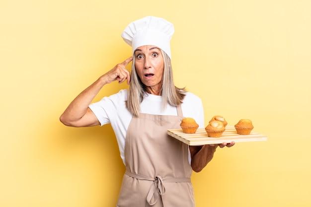Köchin mittleren alters, die überrascht, mit offenem mund, schockiert aussieht, einen neuen gedanken, eine neue idee oder ein neues konzept realisiert und ein muffins-tablett hält