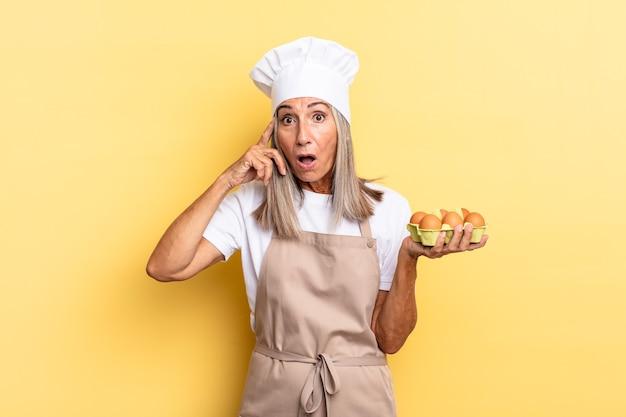 Köchin mittleren alters, die überrascht, mit offenem mund, schockiert aussieht und einen neuen gedanken, eine neue idee oder ein neues konzept mit einer eierschachtel realisiert