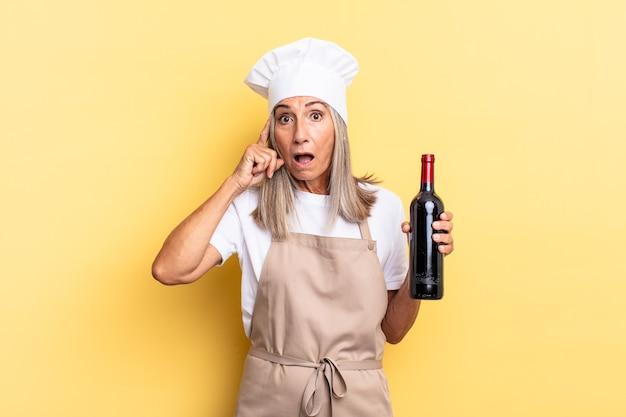 Köchin mittleren alters, die überrascht, mit offenem mund, schockiert aussieht und einen neuen gedanken, eine neue idee oder ein neues konzept mit einer weinflasche realisiert