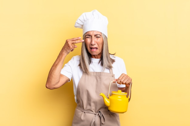 Köchin mittleren alters, die unglücklich und gestresst aussieht, selbstmordgeste, die ein waffenschild mit der hand macht, auf den kopf zeigt und eine teekanne hält