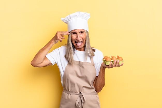 Köchin mittleren alters, die unglücklich und gestresst aussieht, selbstmordgeste, die ein waffenschild mit der hand macht und auf den kopf zeigt, der eine eierschachtel hält