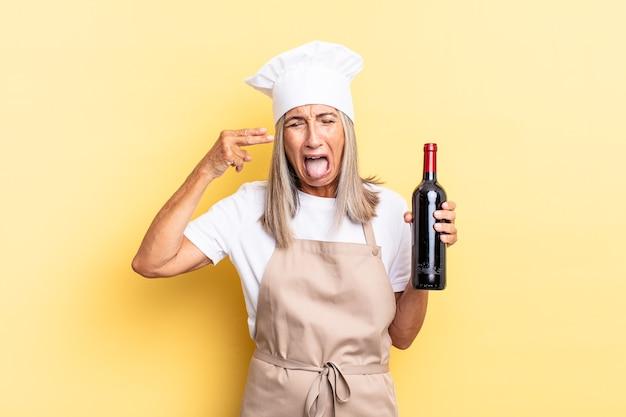 Köchin mittleren alters, die unglücklich und gestresst aussieht, selbstmordgeste, die ein waffenschild mit der hand macht und auf den kopf zeigt, der eine weinflasche hält?