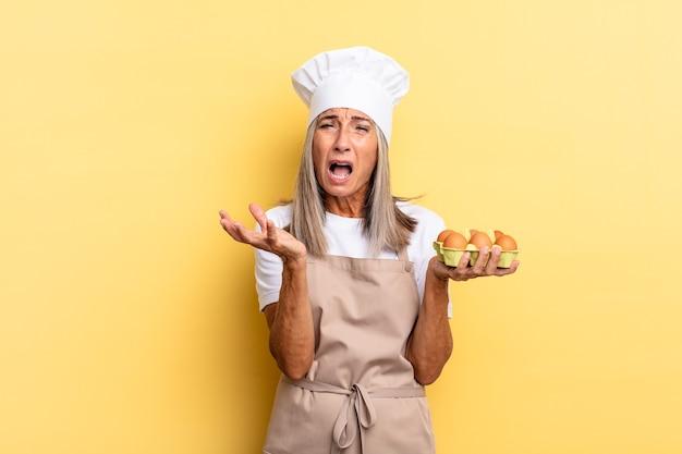 Köchin mittleren alters, die verzweifelt und frustriert, gestresst, unglücklich und genervt aussieht, schreit und schreit und eine eierschachtel hält