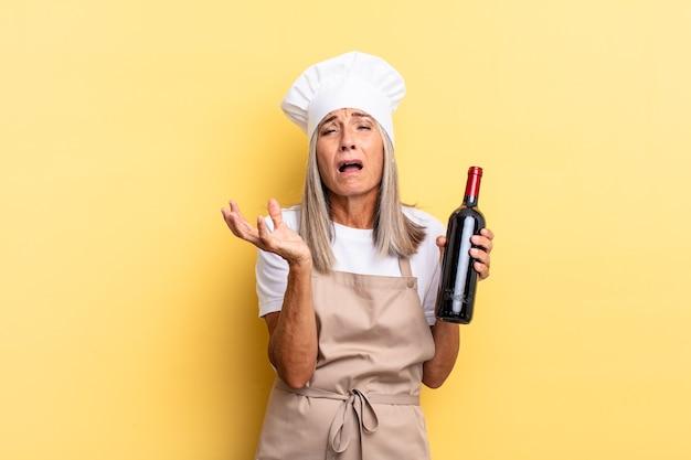 Köchin mittleren alters, die verzweifelt und frustriert, gestresst, unglücklich und verärgert aussieht, schreit und schreit und eine weinflasche hält