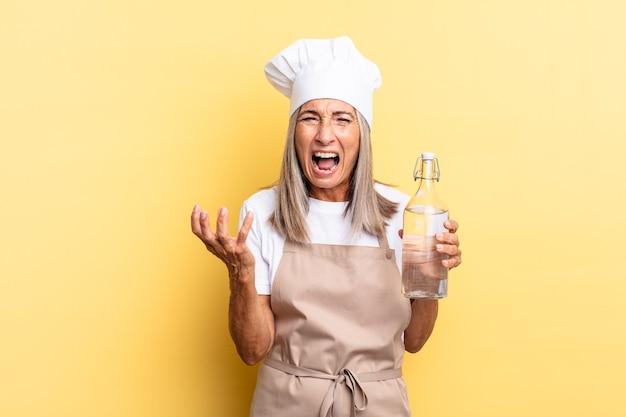 Köchin mittleren alters, die wütend, genervt und frustriert aussieht, schreit wtf oder was ist mit dir mit einer wasserflasche los?