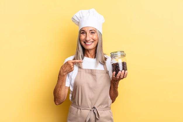 Köchin mittleren alters lächelt fröhlich, fühlt sich glücklich und zeigt zur seite und nach oben, zeigt objekt im kopierraum mit kaffeebohnen
