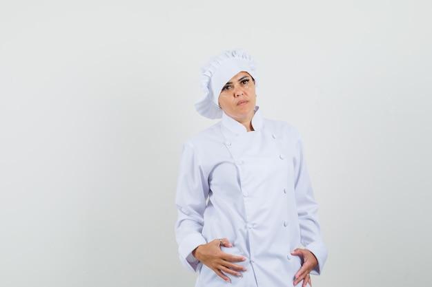 Köchin posiert, während sie in der weißen uniform steht und ernst schaut