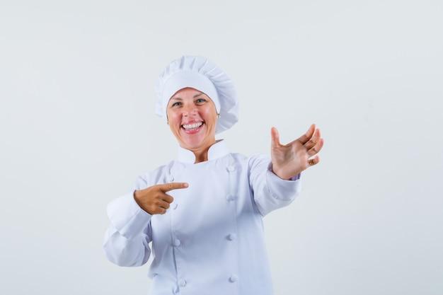 Köchin posiert wie auf telefon in weißer uniform zeigend und sieht fröhlich aus