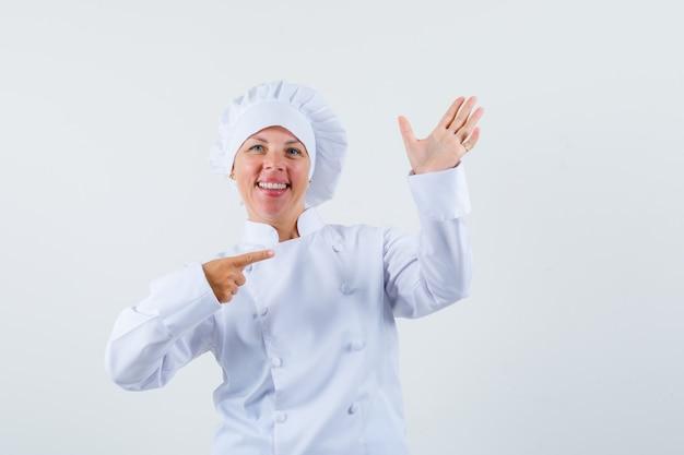 Köchin posiert wie zeigt auf ihre hand, hält telefon in weißer uniform und sieht konzentriert aus.