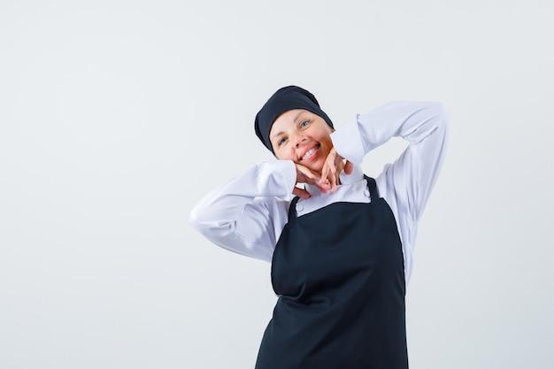 Köchin streckt ellbogen in uniform, schürze und sieht optimistisch aus. vorderansicht.