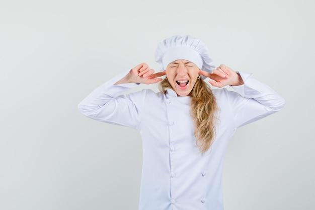 Köchin verstopft ohren mit fingern in weißer uniform und sieht genervt aus
