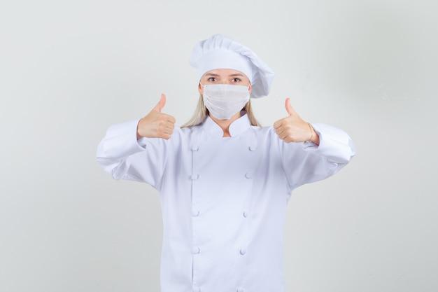 Köchin zeigt daumen hoch in weißer uniform und sieht zufrieden aus