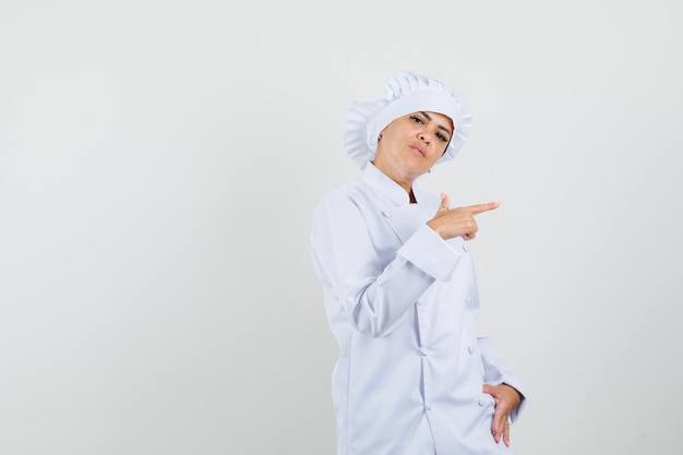 Köchin zeigt zur seite in weißer uniform und sieht ernst aus.