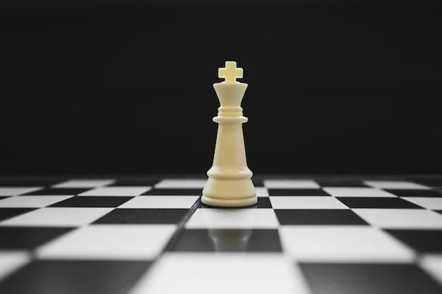 König des siegers auf schachbrettspiel, wettkampf- und strategiekonzept