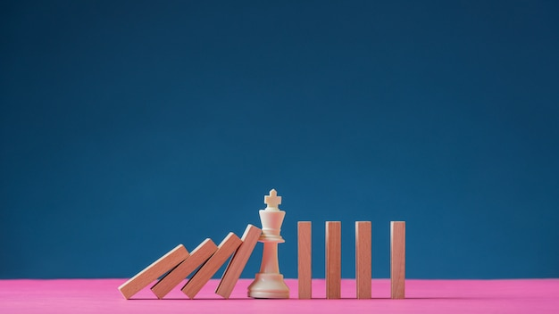 König schachfigur mitten in fallenden dominosteinen
