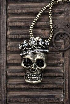Königin- oder königschädel mit krone auf hölzernem hintergrund. halloween dekoration