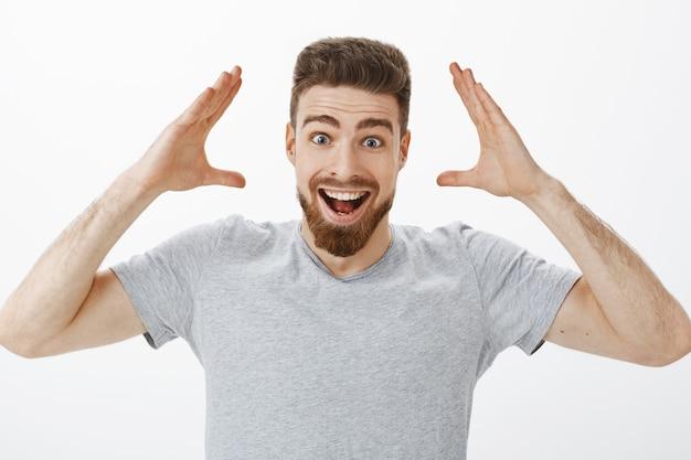 Können sie sich vorstellen, dass ich einen job habe? charismatisches freudiges und aufgeregtes hübsches männliches modell mit bart im grauen t-shirt, das hände nahe dem kopf hebt, breit lächelnd gute nachrichten empfangend und es freunde glücklich nacherzählt