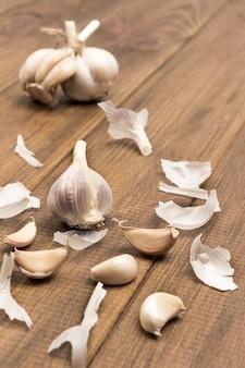 Köpfe und knoblauchzehen auf holztisch. draufsicht. natürliches bäuerliches essen. umweltfreundliches produkt