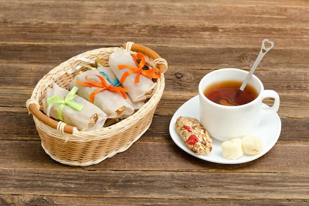 Körbchen mit riegeln, einer tasse schwarzen tees und einer tafel müsli