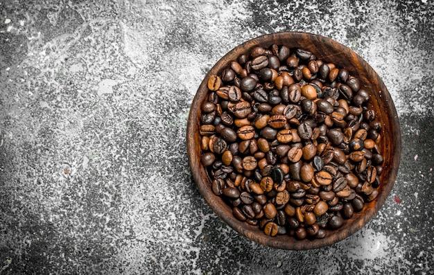 Körner des gebratenen kaffees in einer schüssel auf einem rustikalen hintergrund