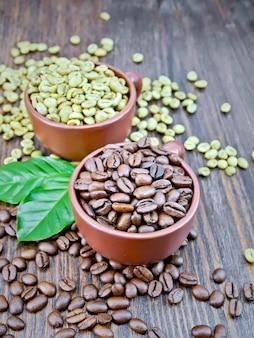Körner von grünem und schwarzem kaffee in braunen tontassen und auf einem tisch mit blättern auf einem hintergrund eines dunklen holzbretts