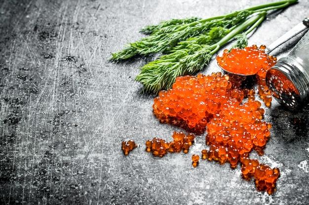 Körner von rotem kaviar mit salz und dill. auf schwarzem rustikalem hintergrund