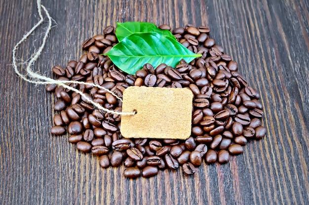 Körner von schwarzem kaffee mit einem etikett und grünen blättern auf einem holzbretthintergrund