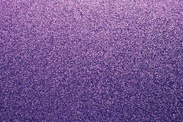 Körniger lila glänzender hintergrund. stoff funkeln, textur. farbverlauf auf textilien, kleidung. glitzerwand. materialmuster, metallisches lametta, dekoration.