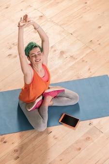 Körper dehnen. fröhliche grünhaarige geschäftsfrau, die ihren körper auf sportmatte streckt