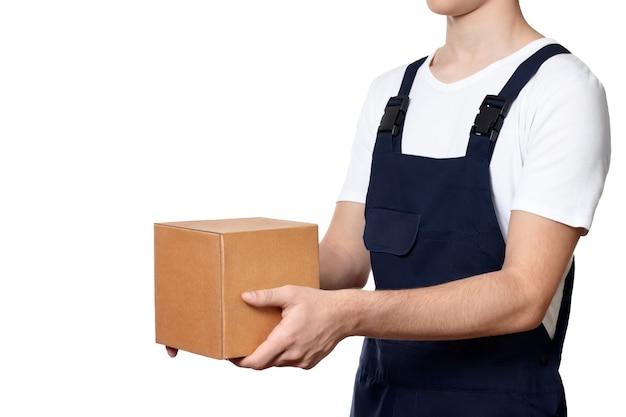 Körper des mannes hält einen karton vor sich hin und überreicht ihn, isoliert auf weißem hintergrund. mann mit paket in dunkelblauen overalls und einem weißen t-shirt. lieferkonzept.