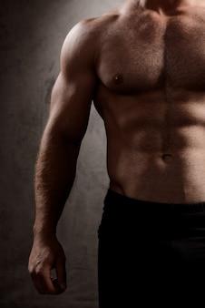 Körper des sportlichen mannes über dunkler wand.