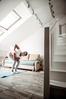 Körper in ordnung. aufmerksame, selbstsüchtige frau, die in yoga-haltung bleibt und ihre hände verbindet