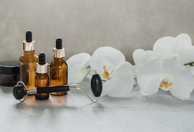 Körper- und hautpflegeprodukte, tropfflaschen und guasha-massagerolle aus obsidianstein im badezimmer mit orchideenblüten, markenmodell für spa-kosmetikprodukte product