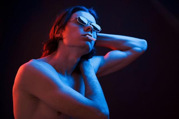Körper zeigen. studioaufnahme im dunklen studio mit neonlicht. porträt eines ernsten mannes