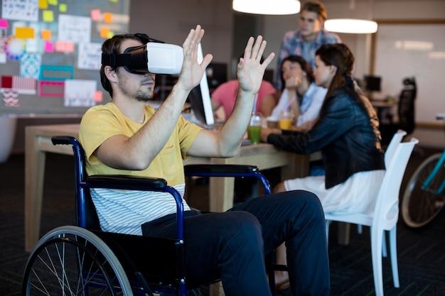 Körperbehinderter mann im rollstuhl mit vr-headset im büro