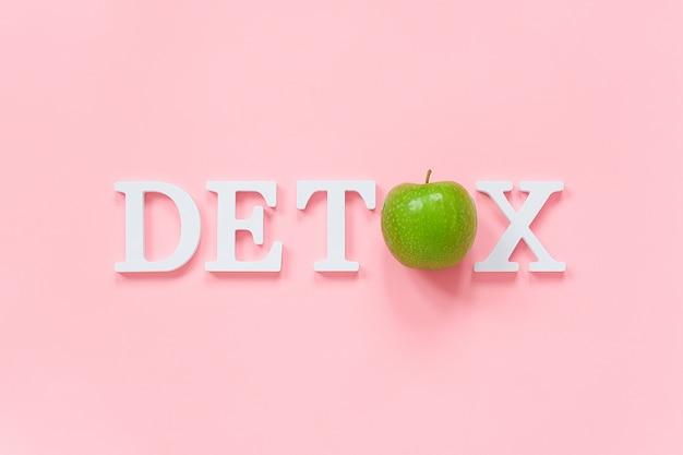 Körperentgiftung und konzept der gesunden diät. grüner natürlicher frischer apfel im wort detox von den weißen buchstaben