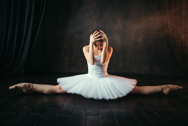 Körperflexibilität des ballettspielers, dehnübung. ballerina im weißen kleid sitzt auf einer schnur auf schwarzem holzboden