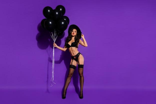 Körpergrößenansicht in voller länge des schönen attraktiven dominanten schicken anmutigen welligen modells, das in den händen hält luftball, der auf hellem lebendigem glanz vibrierend violett lila lila farbhintergrund lokalisiert posiert