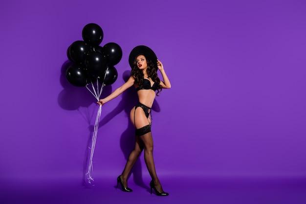 Körpergrößenansicht in voller länge von schöner attraktiver, atemberaubender, wunderschöner, welliger dame, die in den händen einen luftball hält, der isoliert auf hellem, lebendigem, leuchtendem, violettem, lila fliederhintergrund läuft