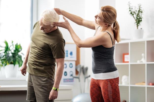 Körperhaltung. angenehme nette frau, die einen männlichen kopf hält, während sie ihm eine korrekte körperhaltung zeigt