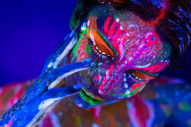 Körperkunst, die im ultravioletten licht leuchtet. körperkunst auf dem körper und der hand eines mädchens, das im ultravioletten licht glüht